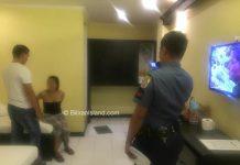 Police agents restrain the female suspect (in black top).